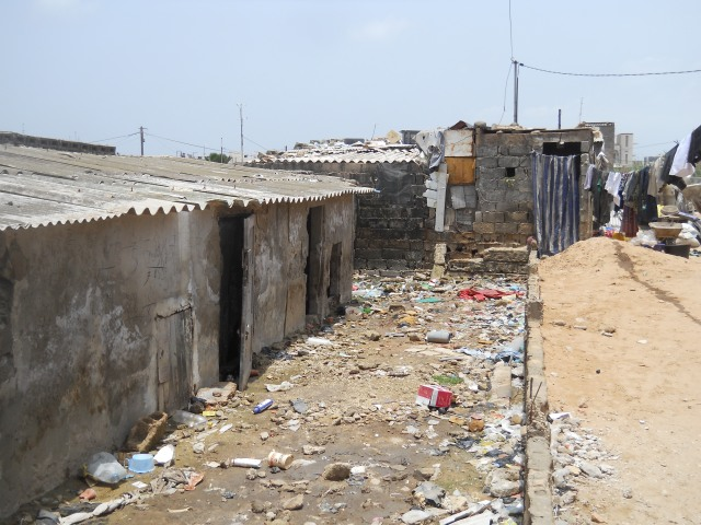 On the left of the image, an abandoned house half buried in a mix of sand, compressed garbage and rubble. To the right, a deposit of sand for a house to soon be built over the embankment, 18/07/2012