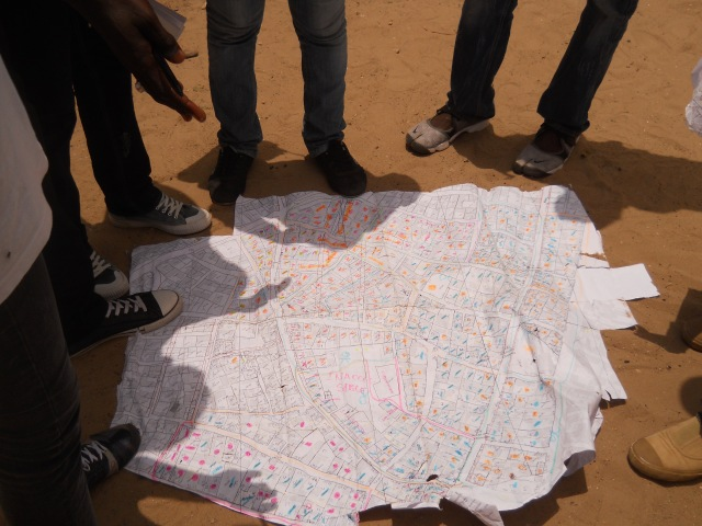 UrbaDTK volunteers, on the field, verifying the accuracy of an initial map produced from household surveys and neighborhood chiefs, 20/07/2012
